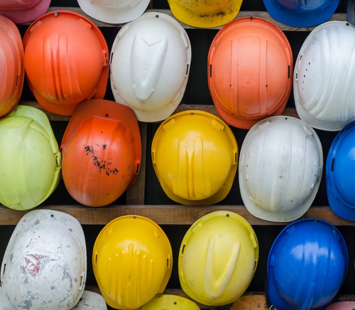 Lots of colorful hardhats photographed from a birds eye view.